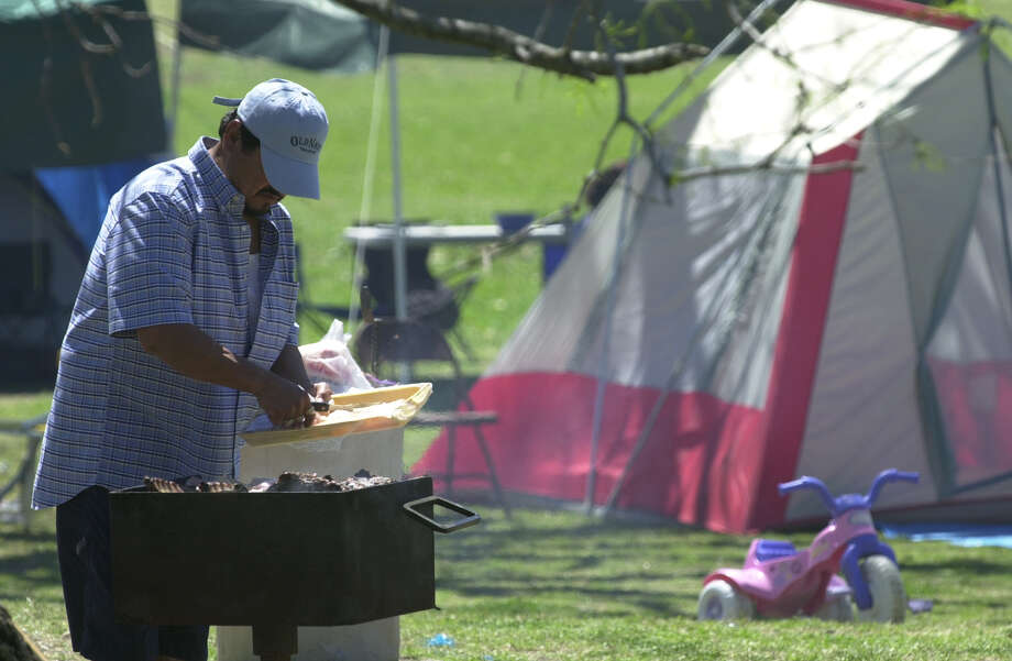 Juan Aleman grills chicken as families enjoy Easter picnics at Brackenridge Park Easter Sunday March 31, 2002.  Photo: ROBERT MCLEROY, SAN ANTONIO EXPRESS-NEWS / SAN ANTONIO EXPRESS-NEWS
