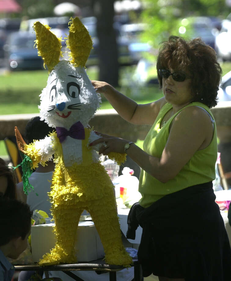 Margaret Skrehot stuffs a pinata as families enjoy Easter picnics at Brackenridge Park Easter Sunday March 31, 2002.  Photo: ROBERT MCLEROY, SAN ANTONIO EXPRESS-NEWS / SAN ANTONIO EXPRESS-NEWS