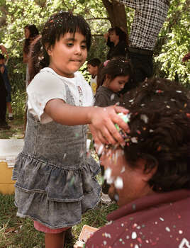 Cecilia Rodriguez, 7, smashes a cascaron on her dad Herminio Rodriguez's head while other children enjoyed looking for hidden Easter eggs at Brackenridge Park in 1998.  Photo: Delcia Lopez, SAN ANTONIO EXPRESS-NEWS / SAN ANTONIO EXPRESS-NEWS