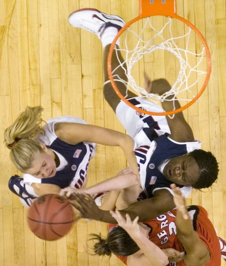 Bridgeport_032606_ Connecticut's Ann Strother, left, Georgia's Megan Darrah, bottom, and Connecticut's Barbara Turner, right, go after a rebound during the 2006 NCAA Tournament Bridgeport Regional basketball tournament at the Arena at Harbor Yard in Bridgeport, Conn. on Sunday, March 26, 2006. Chris Preovolos/Stamford Advocate