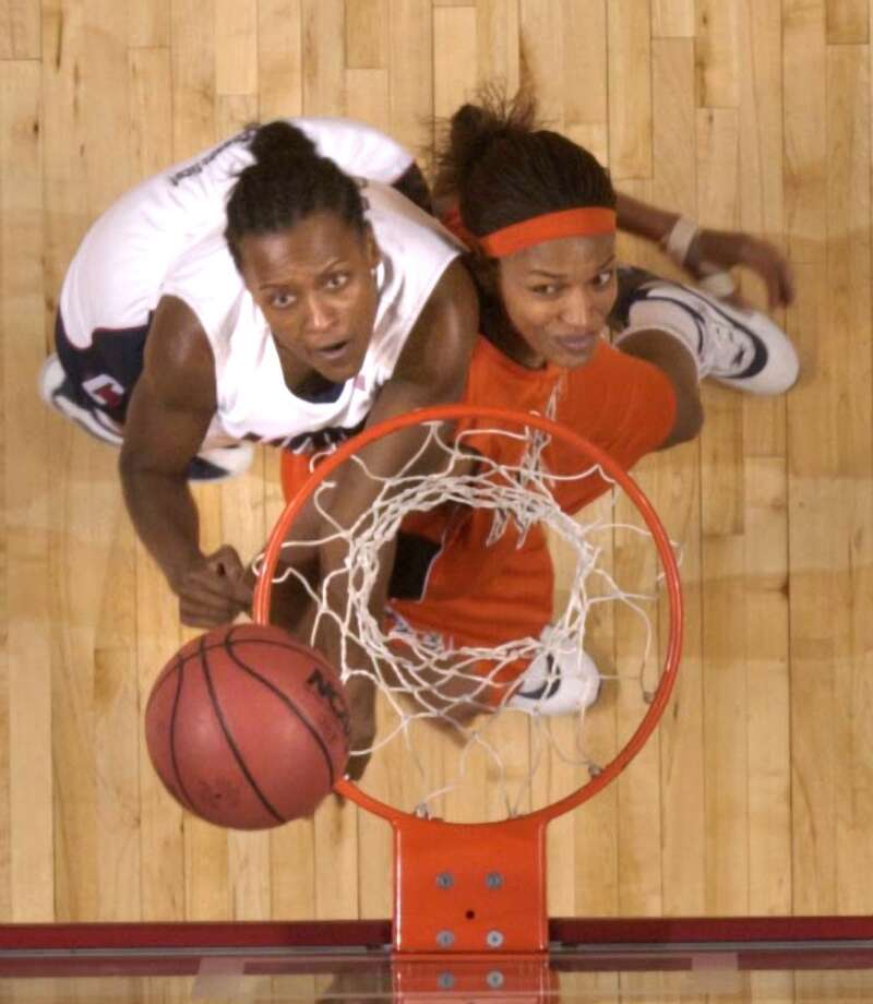 Bridgeport_032304_ University of Connecticut vs. Auburn University in the second round of the NCAA women's basketball tournament. (L) Ashley Battle of UConn fights for a rebound with Auburn's #54, Mandisa Stevenson. Paul Desmarais/Staff photo