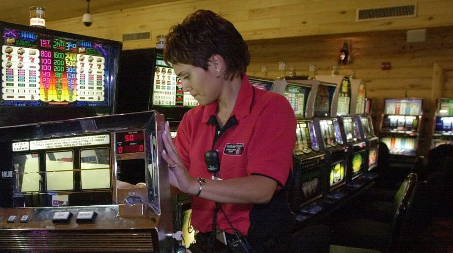Casino employee Terri Roper disables a slot machine at the Alabama-Coushatta casino in the first minutes of Friday, July 26, 2002, at the Alabama-Coushatta Reservation in East Texas. The tribe complied with a court order and shut down at the stroke of midnight Thursday. Photo: PAT SULLIVAN, AP / AP
