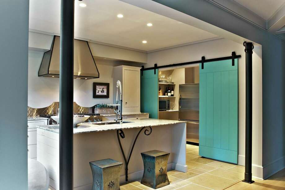 Sliding doors bring a distinctive look to a room. This version is made of planks hanging from exposed hardware. Photo: Charlotte Observer Photos