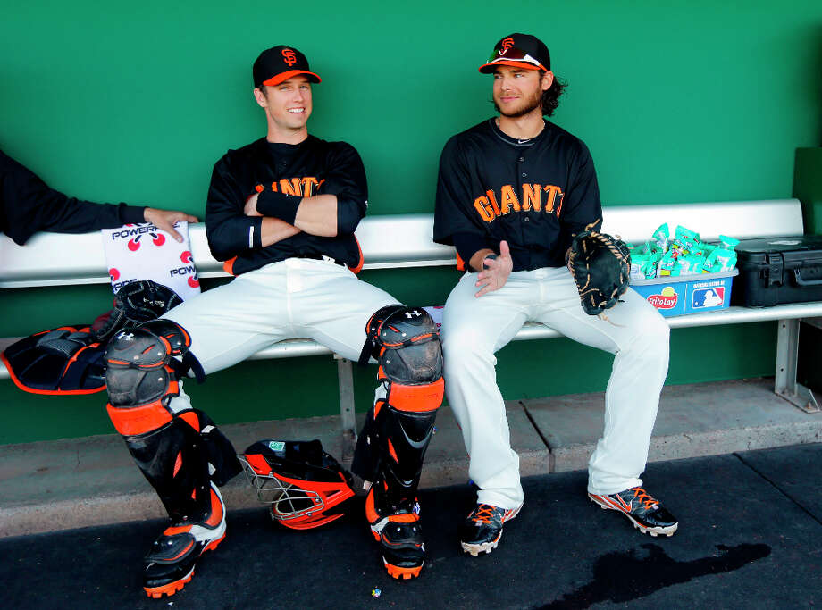 San Francisco Giants catcher Buster Posey, left, and shortstop Brandon Crawford wait in the dugout before an an exhibition spring training baseball game against the Seattle Mariners on Thursday, Feb. 28, 2013 in Scottsdale. Ariz. Photo: Marcio Jose Sanchez, Associated Press / AP