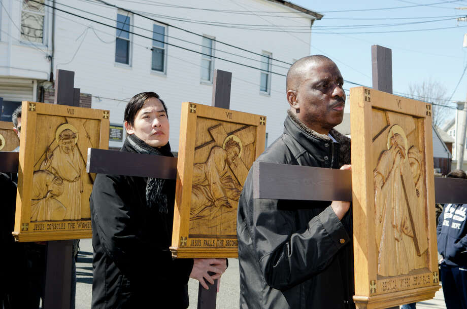"Josn Suyx, of Bridgeport, at left, carries the VII Station of the Cross ""Jesus falls the second time"" as Anthony Appiah, of Bridgeport, carries the VI Station of the Cross ""Veronica wipes Jesus' face"" during the Good Friday processional from St. Augustine's Cathedral to St. Patrick's Church in Bridgeport on Friday, Mar. 29, 2013. Photo: Amy Mortensen / Connecticut Post Freelance"
