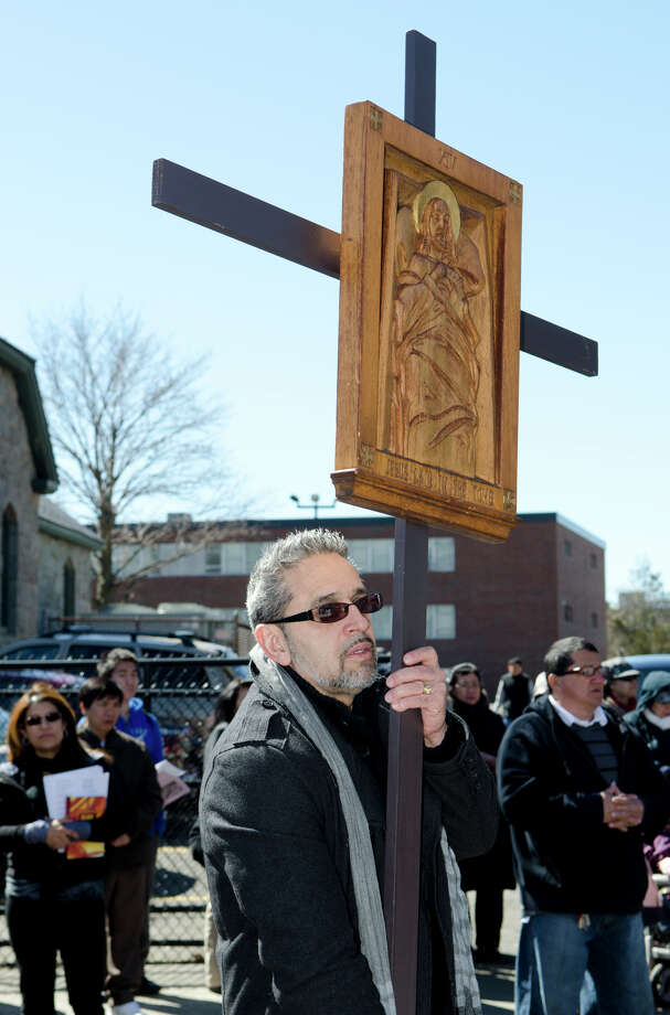 "Johnny Mazo, of Bridgeport, carries the XIV Station of the Cross ""Jesus was laid in the tomb"" during the Good Friday processional from St. Augustine's Cathedral to St. Patrick's Church in Bridgeport on Friday, Mar. 29, 2013. Photo: Amy Mortensen / Connecticut Post Freelance"