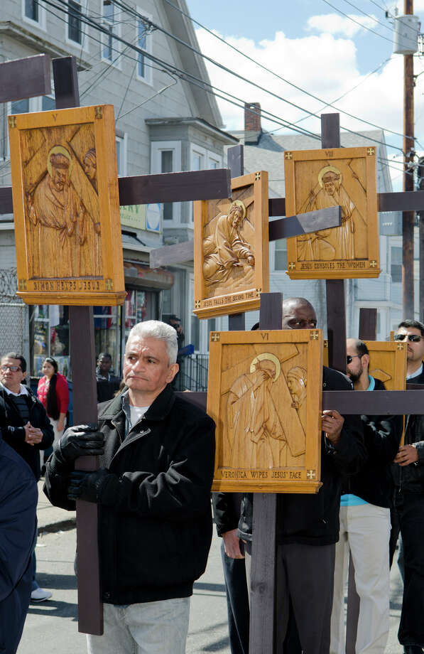"Miguel Pamias, of Bridgeport, carries the V Station of the Cross ""Simon helps Jesus"" during the Good Friday processional from St. Augustine's Cathedral to St. Patrick's Church in Bridgeport on Friday, Mar. 29, 2013. Photo: Amy Mortensen / Connecticut Post Freelance"