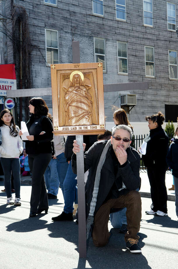 "Johnny Mazo, of Bridgeport, kneels in silent prayer as he carries the XIV Station of the Cross ""Jesus was laid in the tomb"" during the Good Friday processional from St. Augustine's Cathedral to St. Patrick's Church in Bridgeport on Friday, Mar. 29, 2013. Photo: Amy Mortensen / Connecticut Post Freelance"