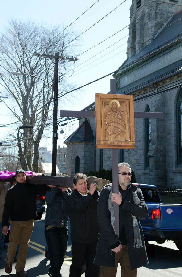 """Johnny Mazo, of Bridgeport, carries the XIV Station of the Cross """"Jesus was laid in the tomb"""" during the Good Friday processional from St. Augustine's Cathedral to St. Patrick's Church in Bridgeport on Friday, Mar. 29, 2013. Photo: Amy Mortensen / Connecticut Post Freelance"""
