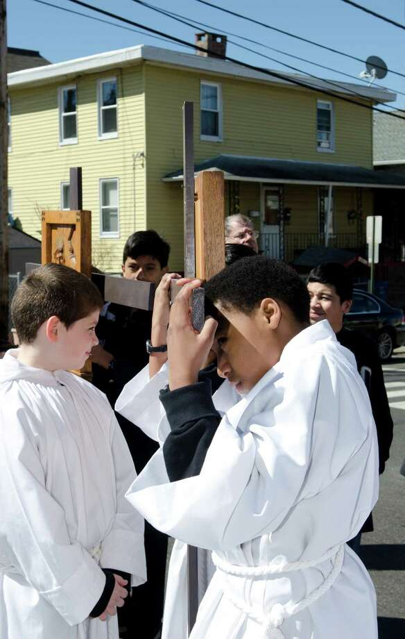 Isaiah Smith, 12, of St. Patrick's, rests his head on the Station of the Cross during the Good Friday processional from St. Augustine's Cathedral to St. Patrick's Church in Bridgeport on Friday, Mar. 29, 2013. Photo: Amy Mortensen / Connecticut Post Freelance