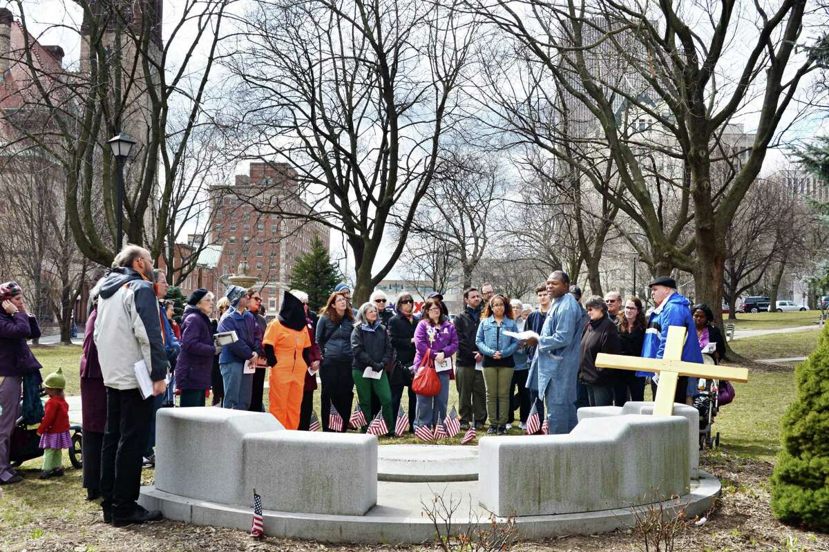 Paul Besong of Cameroon joins local Christians to pray for an end to suffering during Outdoor Stations of the Cross sponsored by the Albany Catholic Worker Community in Albany March 29, 2013. (John Carl D'Annibale / Times Union)