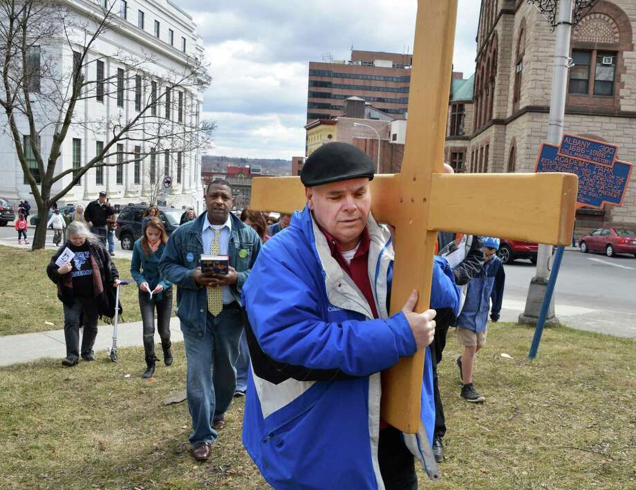 Ed Falterman of Albany Catholic Worker and Our Lady of the Americas Shrine carries a cross as local Christians pray for an end to suffering during Outdoor Stations of the Cross in Albany March 29, 2013.   (John Carl D'Annibale / Times Union) Photo: John Carl D'Annibale / 00021739A