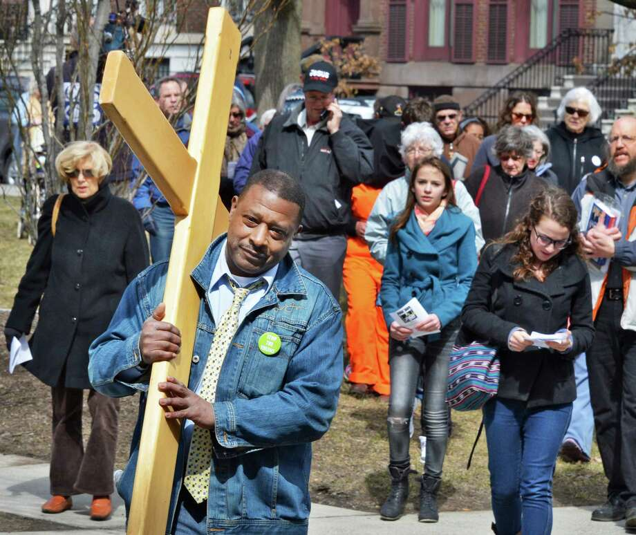 Willie White of A Village, Albany carries a cross as local Christians pray for an end to suffering during Outdoor Stations of the Cross sponsored by the Albany Catholic Worker Community in Albany March 29, 2013.   (John Carl D'Annibale / Times Union) Photo: John Carl D'Annibale / 00021739A