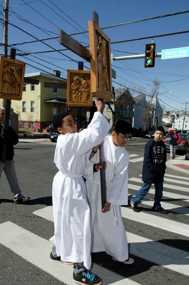"Isaiah Smith, 12, of St. Patrick's, and Elton Tonncato, 12, of St. Augustine's Cathedral, work together to carry the II Station of the Cross ""Jesus made to bear his cross"" during the Good Friday processional from St. Augustine's Cathedral to St. Patrick's Church in Bridgeport on Friday, Mar. 29, 2013. Photo: Amy Mortensen / Connecticut Post Freelance"