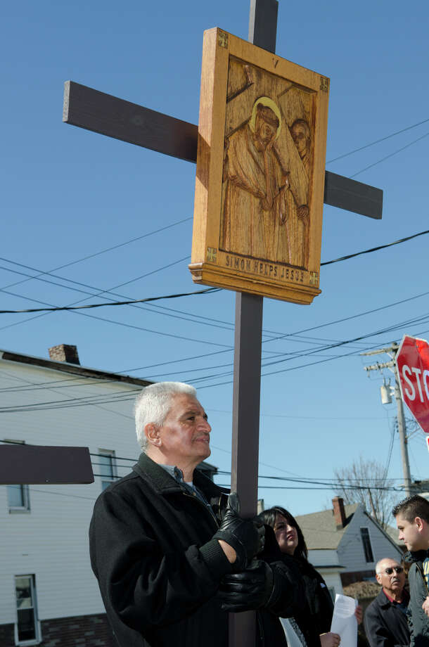 """Miguel Pamias, of Bridgeport, carries the V Station of the Cross """"Simon helps Jesus"""" during the Good Friday processional from St. Augustine's Cathedral to St. Patrick's Church in Bridgeport on Friday, Mar. 29, 2013. Photo: Amy Mortensen / Connecticut Post Freelance"""