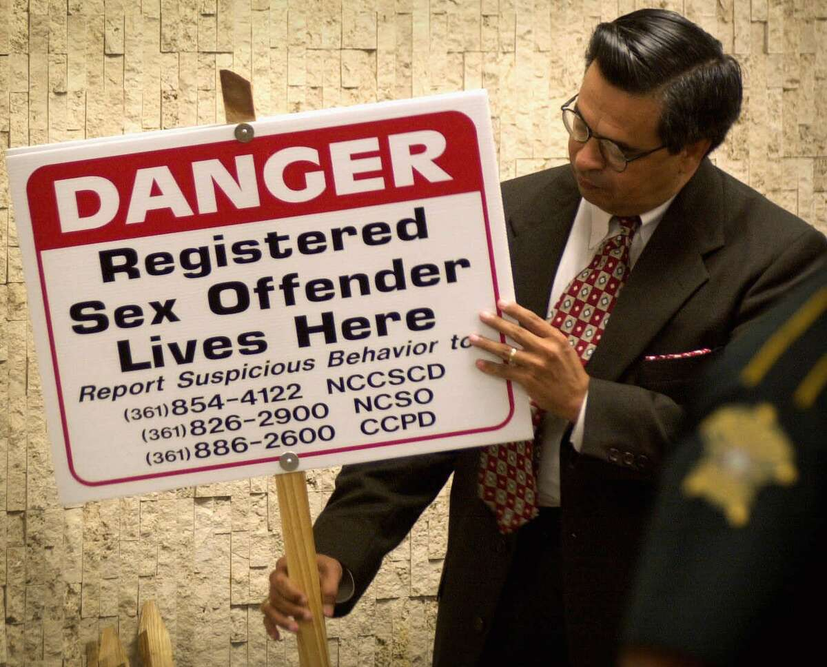 File - In This May 18, 2001 file photo, Nueces County Texas District Attorney Carlos Valdez looks at one of the signs that District Judge Manuel Banales ordered 21 registered sex offenders to place in their yards in Corpus Christi, Texas. While statehouses nationwide work on legislation aimed at curbing how and where sex offenders can live and work, a proposal in Texas that would strip employment information from the state's sex offender registry is being cheered by those on the list as a minor but extraordinary easing of the law.