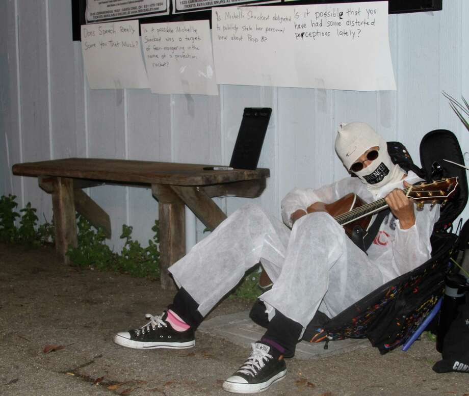Alternative folk singer Michelle Shocked sits outside Moe's Alley nightclub in Santa Cruz Calif., and strums her guitar on Thursday, March 28, 2013. After her show was canceled when she made an anti-gay slur earlier this month. Shocked had her face covered and her mouth taped shut. She dressed in a white disposable safety suit and invited people to write on it. (AP Photo Photo: THOMAS VINCENT MENDOZA