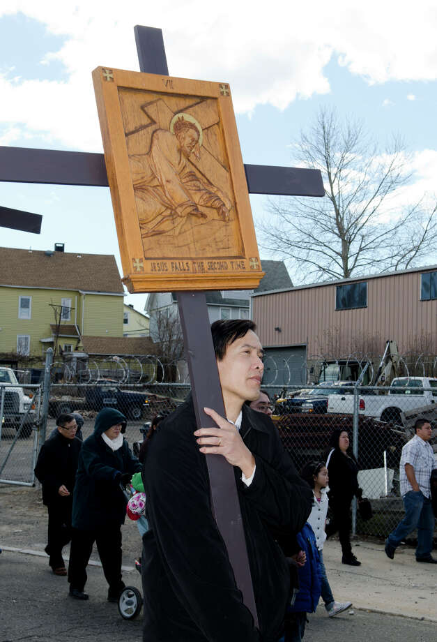 "Josn Suyx, of Bridgeport, at left, carries the VII Station of the Cross ""Jesus falls the second time"" during the Good Friday processional from St. Augustine's Cathedral to St. Patrick's Church in Bridgeport on Friday, Mar. 29, 2013. Photo: Amy Mortensen / Connecticut Post Freelance"