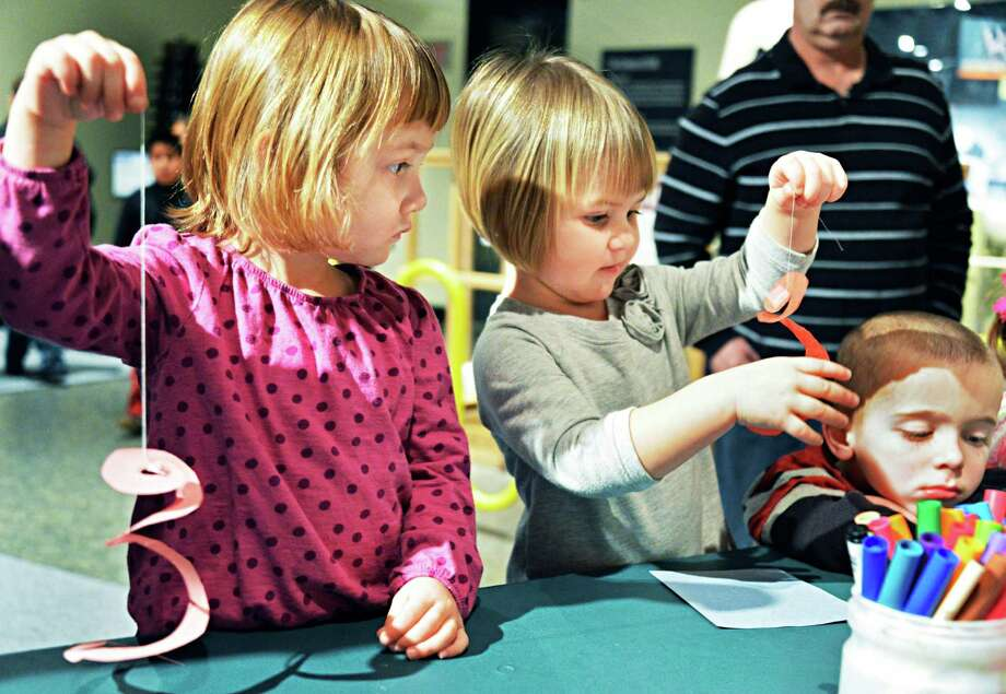 Making whirligigs to test heat's affect on air movement are , from left, Sofia Lozynsky, 3, of WatervlietAleni Harriman, 2, of Niskayuna, and Branden Redick, 4, of Albany at the Science Zone in the Museum of Innovation and Science in Schenectady Wednesday Feb. 20, 2013.  (John Carl D'Annibale / Times Union) Photo: John Carl D'Annibale / 00021149A