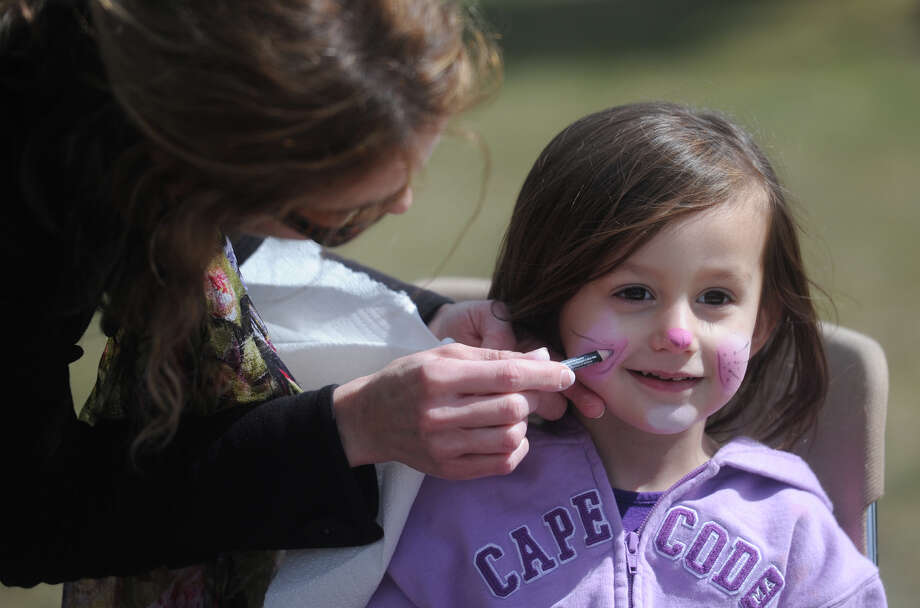 Lucia Lorant, 3, of Trumbull, gets her face painted by Alison Cummings, of Newtown, at the Bunny Watch Hayride at Glander Field Pavilion in Newtown, Conn. on Friday, March 29, 2013.  Hundreds of people enjoyed the scenic hayride on antique tractors while counting the stuffed-animal bunnies hiding in the woods along the way. The Easter Bunny greeted the children halfway through the ride, giving hugs and handshakes.  Also available was a bounce house, slide, face painting and many other children's activities. Photo: Tyler Sizemore / The News-Times