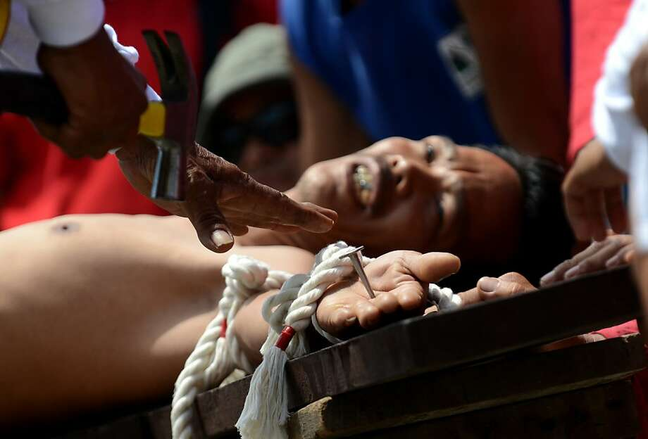 A penitent is nailed to a crossduring a realistic Good Friday re-enactment of the Crucifixion in the Philippine village of San Juan, San Fernando City. The Roman Catholic Church in the Philippines frowns on such bloody displays of religious fanaticism. Photo: Noel Celis, AFP/Getty Images