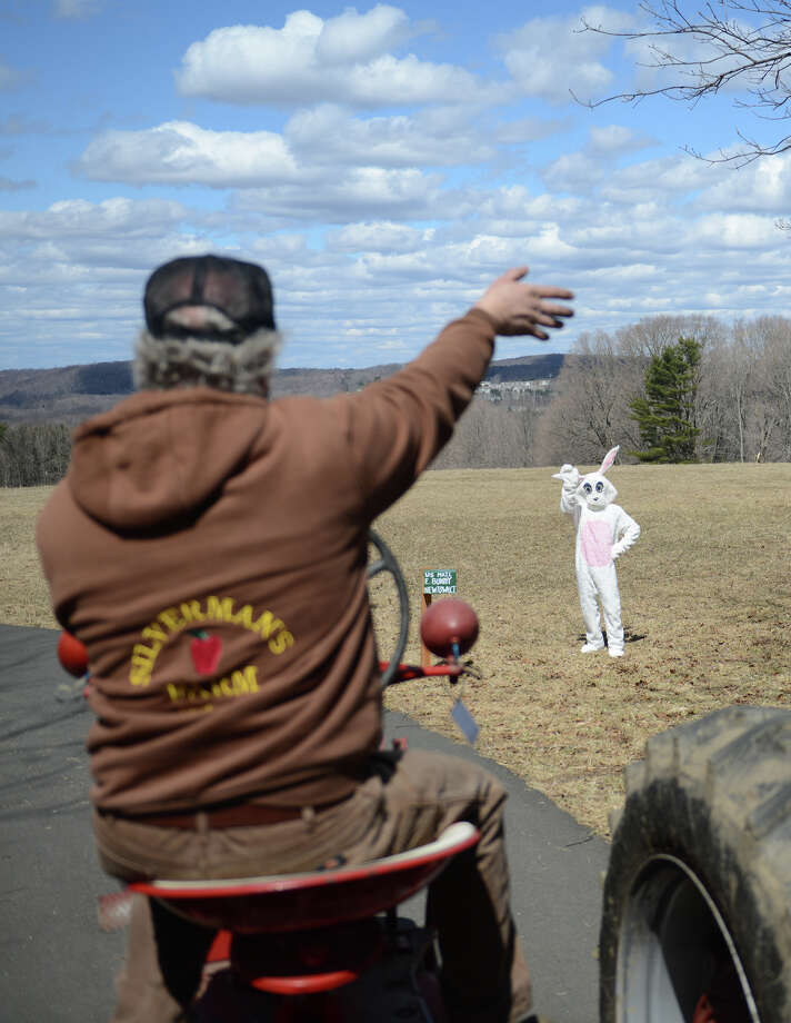 The Easter Bunny waves to hayride driver Rob Emmerthal, of Newtown, on the Bunny Watch Hayride at Glander Field Pavilion in Newtown, Conn. on Friday, March 29, 2013.  Hundreds of people enjoyed the scenic hayride on antique tractors while counting the stuffed-animal bunnies hiding in the woods along the way. The Easter Bunny greeted the children halfway through the ride, giving hugs and handshakes.  Also available was a bounce house, slide, face painting and many other children's activities. Photo: Tyler Sizemore / The News-Times