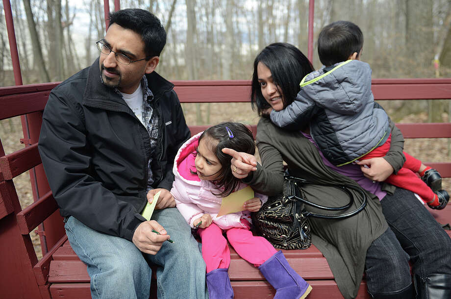 From left, Kalpesh Patel, Jaanvi Patel, 3, Parul Patel, and Shiv Patel, 2, of Newtown, spot bunnies on the Bunny Watch Hayride at Glander Field Pavilion in Newtown, Conn. on Friday, March 29, 2013.  Hundreds of people enjoyed the scenic hayride on antique tractors while counting the stuffed-animal bunnies hiding in the woods along the way. The Easter Bunny greeted the children halfway through the ride, giving hugs and handshakes.  Also available was a bounce house, slide, face painting and many other children's activities. Photo: Tyler Sizemore / The News-Times