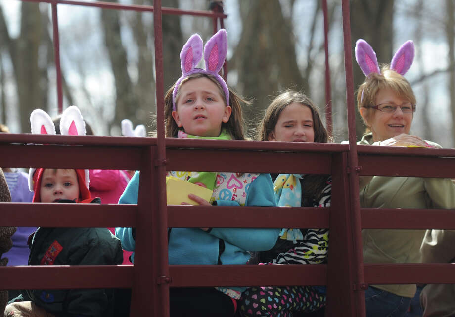 From left, Liam Bishop, 2, of Monroe, Gwenny Bishop, 8, of Monroe, Alexis Wasic, 8, of Newtown, and Linda Tremalio, of Shelton, look for bunnies on the Bunny Watch Hayride at Glander Field Pavilion in Newtown, Conn. on Friday, March 29, 2013.  Hundreds of people enjoyed the scenic hayride on antique tractors while counting the stuffed-animal bunnies hiding in the woods along the way. The Easter Bunny greeted the children halfway through the ride, giving hugs and handshakes.  Also available was a bounce house, slide, face painting and many other children's activities. Photo: Tyler Sizemore / The News-Times