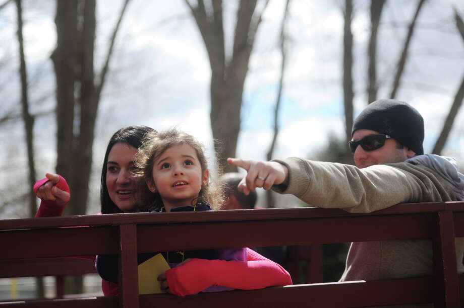 Loralee, left, Alayna, 3, and Josh Richter, of Brookfield, spot bunnies on the Bunny Watch Hayride at Glander Field Pavilion in Newtown, Conn. on Friday, March 29, 2013.  Hundreds of people enjoyed the scenic hayride on antique tractors while counting the stuffed-animal bunnies hiding in the woods along the way. The Easter Bunny greeted the children halfway through the ride, giving hugs and handshakes.  Also available was a bounce house, slide, face painting and many other children's activities. Photo: Tyler Sizemore / The News-Times