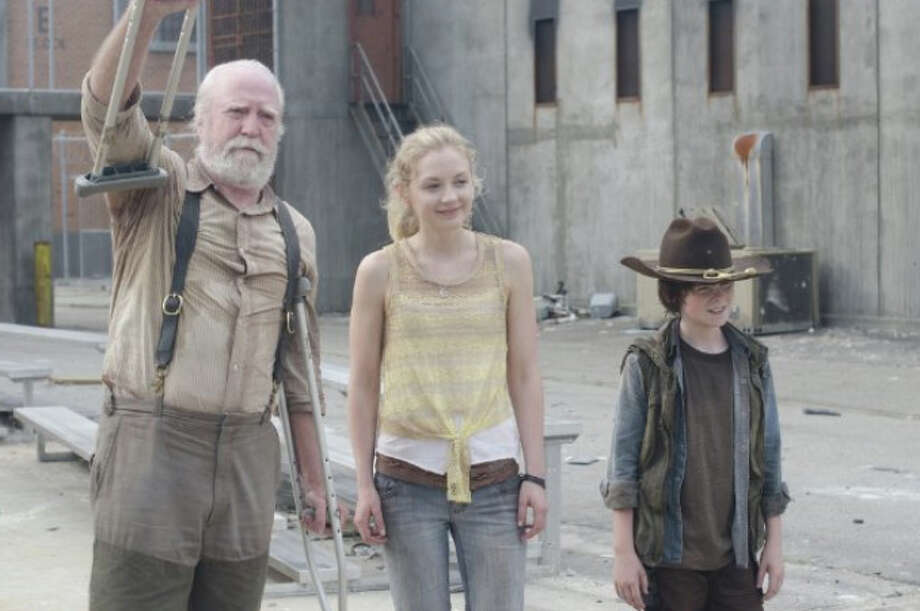 Here's what Emily Kinney, center, looks like on the show, as Beth Greene, daughter of Hershel (Scott Wilson, left).