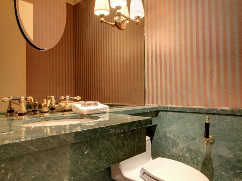 Powder room of 11 Comstock St. The 4,190-square-foot house, built in 1991, has four bedrooms, 3.5 bathrooms, a two-story entry, marble floors, walls of windows, a wood-paneled library, decks, a patio, city and water views, and a two-car garage on a 5,197-square-foot lot. It's listed for $1.799 million. Photo: Courtesy Colleen McCann/Windermere Real Estate