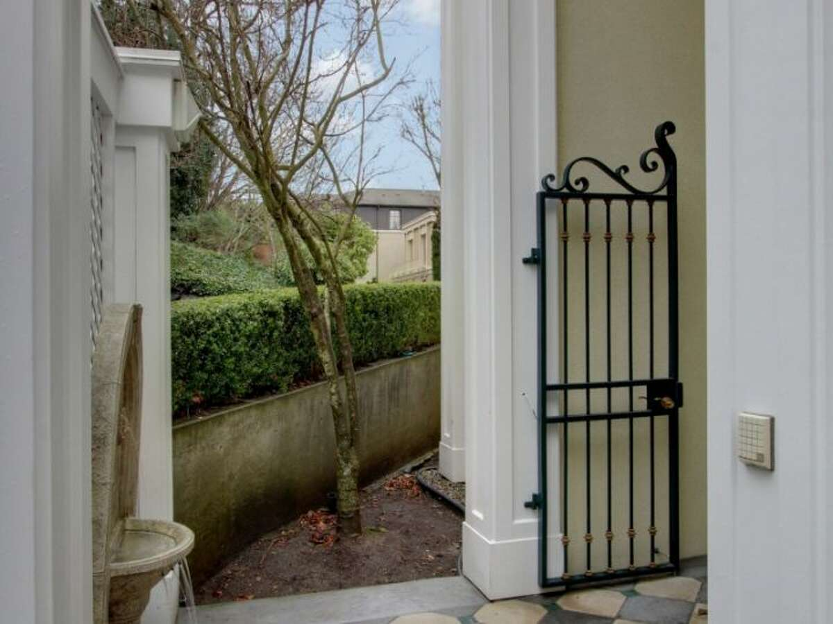 Gate of 11 Comstock St. The 4,190-square-foot house, built in 1991, has four bedrooms, 3.5 bathrooms, a two-story entry, marble floors, walls of windows, a wood-paneled library, decks, a patio, city and water views, and a two-car garage on a 5,197-square-foot lot. It's listed for $1.799 million.
