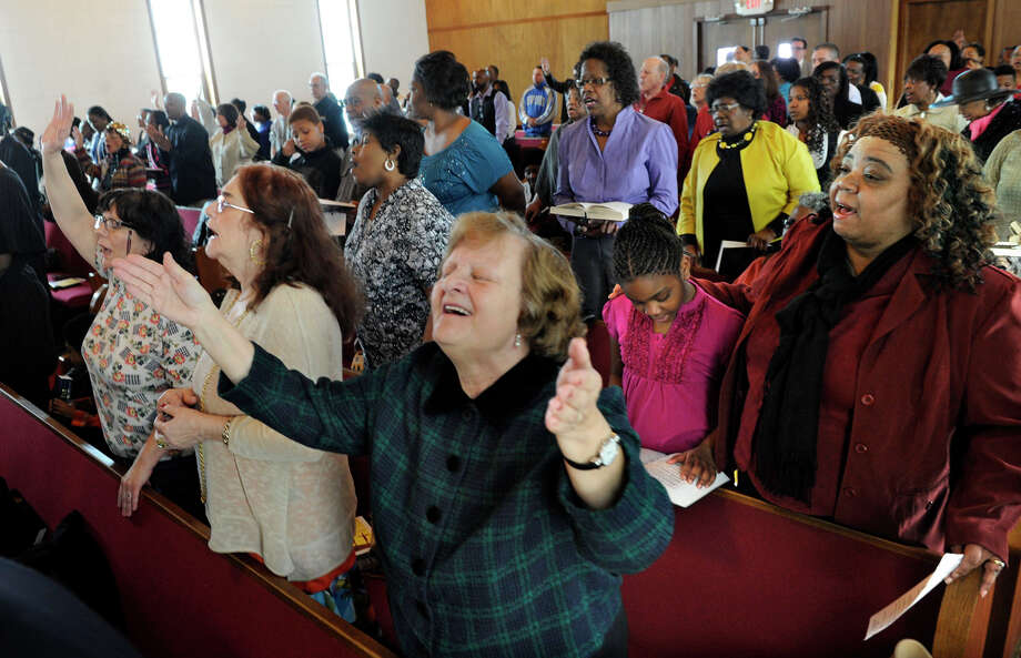 "Maryanne McTonic, of Bethel, center, worships during a Good Friday service hosted by Mount Pleasant A.M.E. Zion Church on Rowan Street in Danbury, Conn., March 29, 2013. A total of ten area churches participated in the noon service that explored Christ's ""Seven Last Words from the Cross."" Photo: Carol Kaliff / The News-Times"