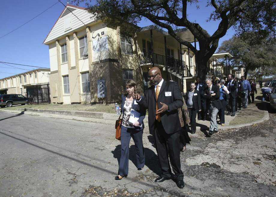 Jane Hodgdon of the Department of Education speaks with Tony Leverett during a tour of Wheatley Courts. Photo: Helen L. Montoya / San Antonio Express-News