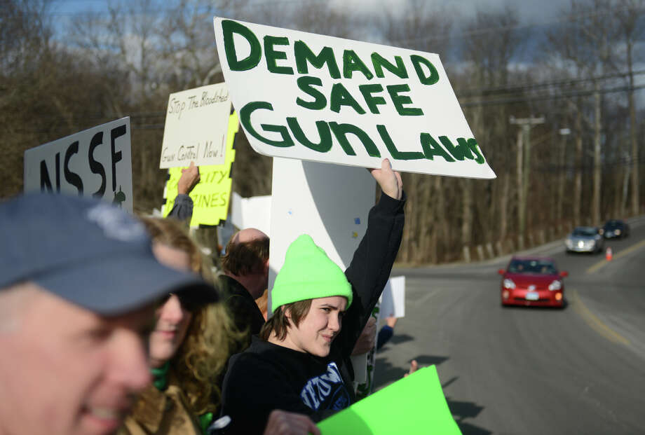 Brady Eggleston, of Newtown, holds up a sign at the Newtown Action Alliance rally outside of the National Shooting Sports Foundation headquarters in Newtown, Conn. on Thursday, March 28, 2013.  The rally was attended by supporters of gun reform, as well as many members of the NRA.  The two groups cooperated peacefully together, with gun reform supporters outnumbering NRA supporters by about a two to one ratio.  More than 100 combined demonstrators attended the rally. Photo: Tyler Sizemore / The News-Times
