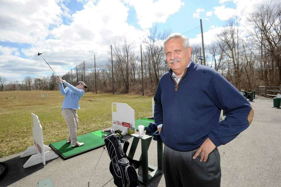 At right, David D'Andrea, operations manager of the town-owned Griffith E. Harris Golf Course in Greenwich, stands near the driving range next to golfer Todd Leih of Greenwich who is about to hit the ball, Friday, March 29, 2013. The safety net behind D'Andrea was damaged during Hurricane Sandy and recently replaced. Photo: Bob Luckey / Greenwich Time
