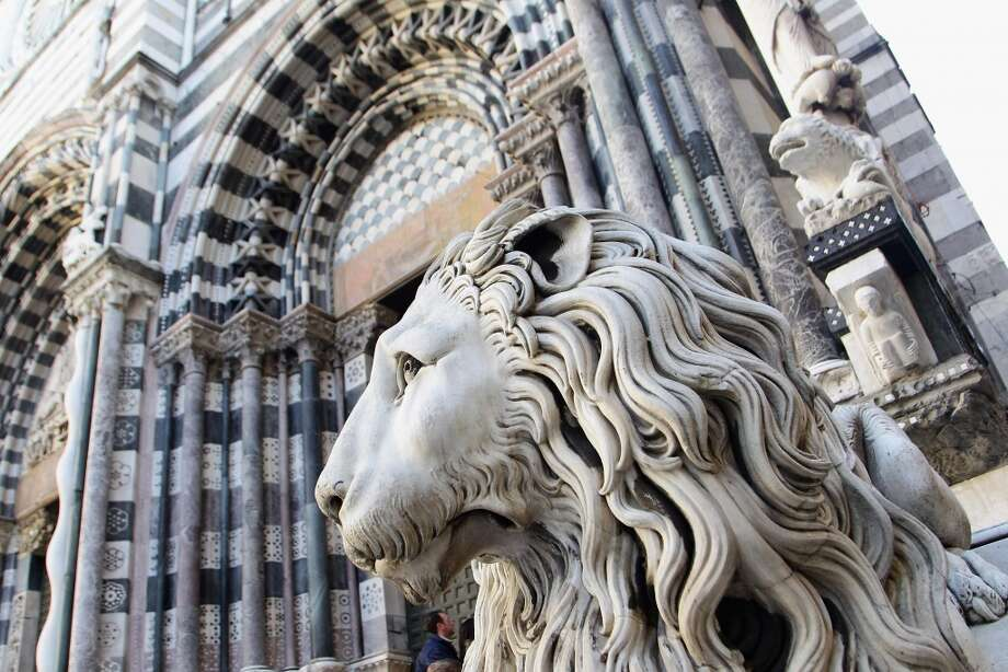 A lion guards the entrance to the Cattedrale di San Lorenzo.