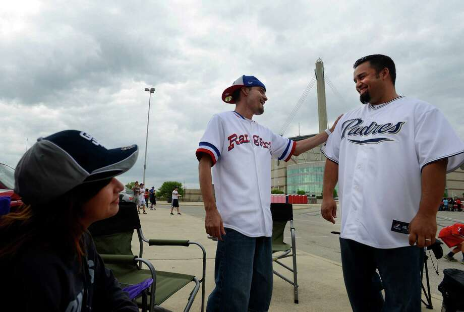 Mariah Cavazos, left, and her uncle Joseph Cavazos and father Tony Cavazos tailgate before the San Diego Padres  versus Texas Rangers Big League Weekend game at the Alamodome on Friday, March 29, 2013.  The family is split on their team loyalties. Photo: Billy Calzada, San Antonio Express-News / San Antonio Express-News