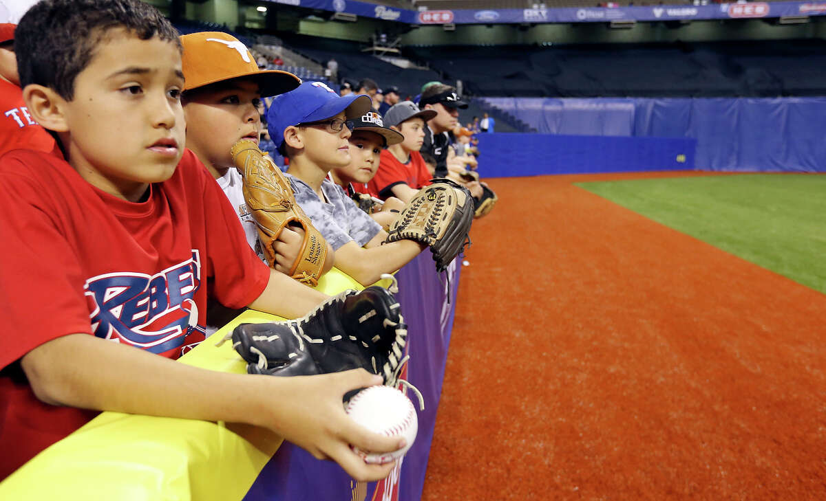 Baseball fans Brandon Garcia, 10, (from left), Frankie Garza, 10, and others wait for balls during batting practice before the Texas Rangers and San Diego Padres game part of the ?'Big League Weekend?