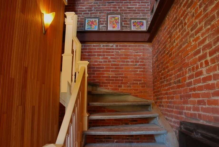Staircase of 819 Washington St., in Port Townsend. The 2,700-square-foot brick building, erected as a cracker factory in in 1888, has one bedroom suite, which takes up the entire third floor, 1.25 bathrooms, a ground-floor workspace, exposed brick walls, wood ceilings, tile floors, a carved limestone fireplace and a roof deck. It's listed for $937,770. Photo: Josh Phoenix/HD Estates,  Courtesy Michelle Sandoval/Windermere Real Estate