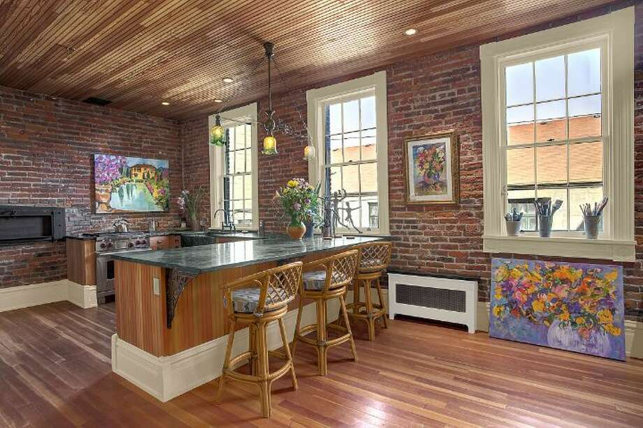 Kitchen of 819 Washington St., in Port Townsend. The 2,700-square-foot brick building, erected as a cracker factory in in 1888, has one bedroom suite, which takes up the entire third floor, 1.25 bathrooms, a ground-floor workspace, exposed brick walls, wood ceilings, tile floors, a carved limestone fireplace and a roof deck. It's listed for $937,770. Photo: Josh Phoenix/HD Estates,  Courtesy Michelle Sandoval/Windermere Real Estate