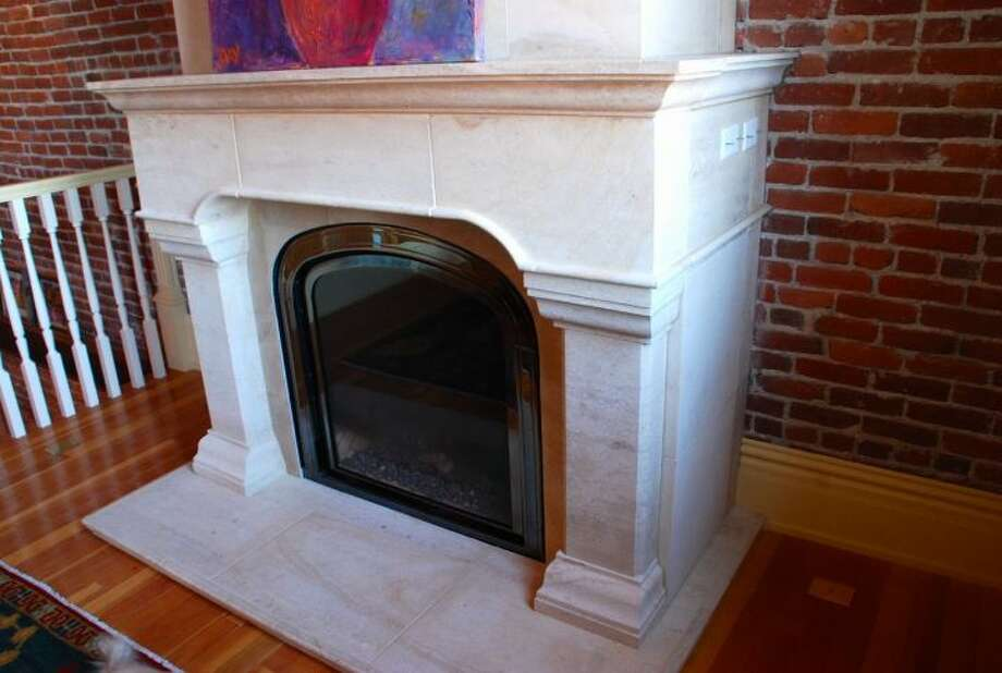 Carved limestone fireplace of 819 Washington St., in Port Townsend. The 2,700-square-foot brick building, erected as a cracker factory in in 1888, has one bedroom suite, which takes up the entire third floor, 1.25 bathrooms, a ground-floor workspace, exposed brick walls, wood ceilings, tile floors and a roof deck. It's listed for $937,770. Photo: Josh Phoenix/HD Estates,  Courtesy Michelle Sandoval/Windermere Real Estate
