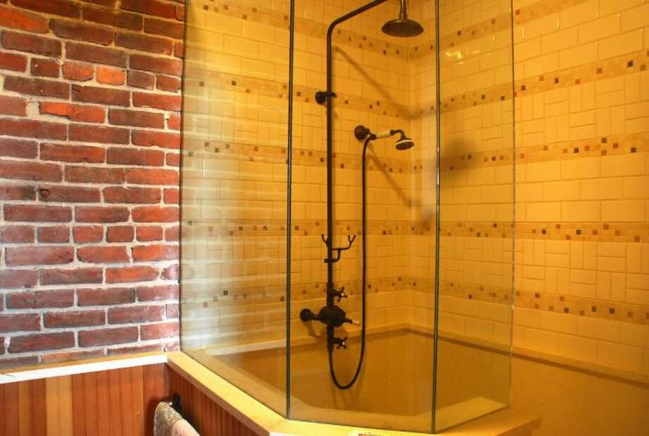 Bathroom of 819 Washington St., in Port Townsend. The 2,700-square-foot brick building, erected as a cracker factory in in 1888, has one bedroom suite, which takes up the entire third floor, 1.25 bathrooms, a ground-floor workspace, exposed brick walls, wood ceilings, tile floors, a carved limestone fireplace and a roof deck. It's listed for $937,770. Photo: Josh Phoenix/HD Estates,  Courtesy Michelle Sandoval/Windermere Real Estate