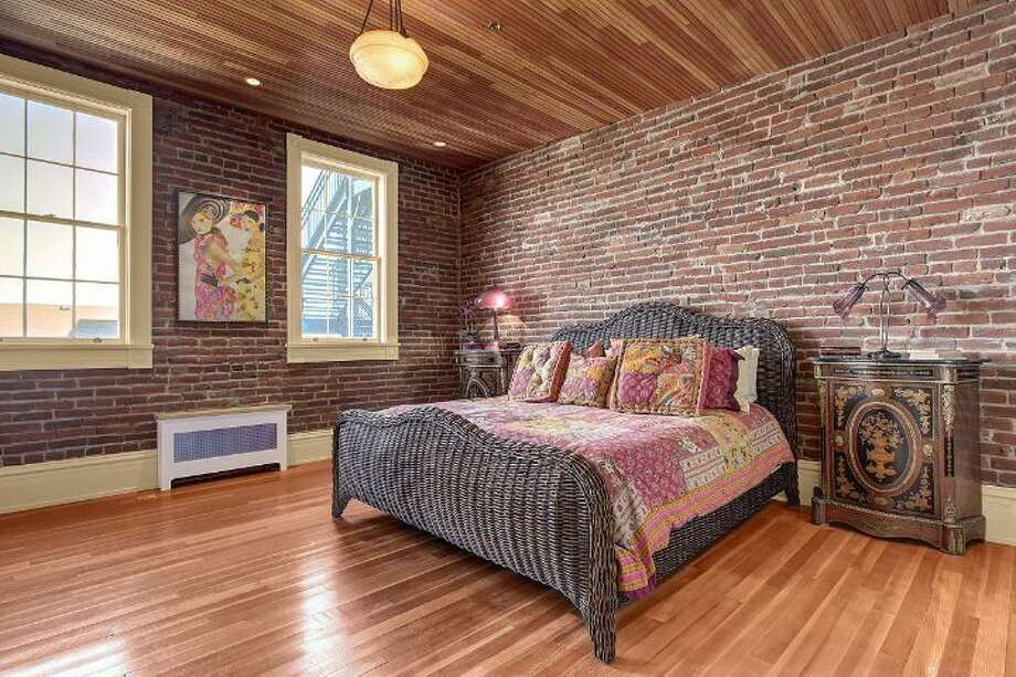 Bedroom suite of 819 Washington St., in Port Townsend. The 2,700-square-foot brick building, erected as a cracker factory in in 1888, has one bedroom, 1.25 bathrooms, a ground-floor workspace, exposed brick walls, wood ceilings, tile floors, a carved limestone fireplace and a roof deck. It's listed for $937,770. Photo: Josh Phoenix/HD Estates,  Courtesy Michelle Sandoval/Windermere Real Estate