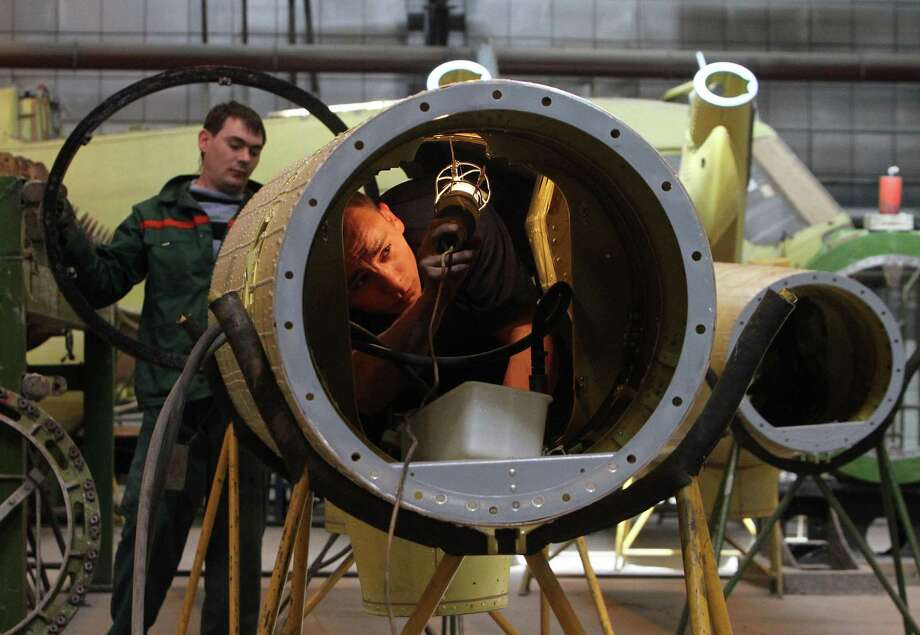 "An employee uses a light to inspect the interior of a Mi-17 helicopter section in the intermediate assembly shop at the JSC Kazan Helicopters factory, operated by JSC ""Russian Helicopters,"" in Kazan, Russia, on Thursday, May 12, 2011. ""Russian Helicopters,"" a leading global designer and manufacturer of helicopters, and producer of some of the world's most iconic, innovative and widely operated models, announced that its offering of ordinary shares and GDRs has been postponed. Photographer: Andrey Rudakov/Bloomberg Photo: Andrey Rudakov, Bloomberg / © 2011 Bloomberg Finance LP"