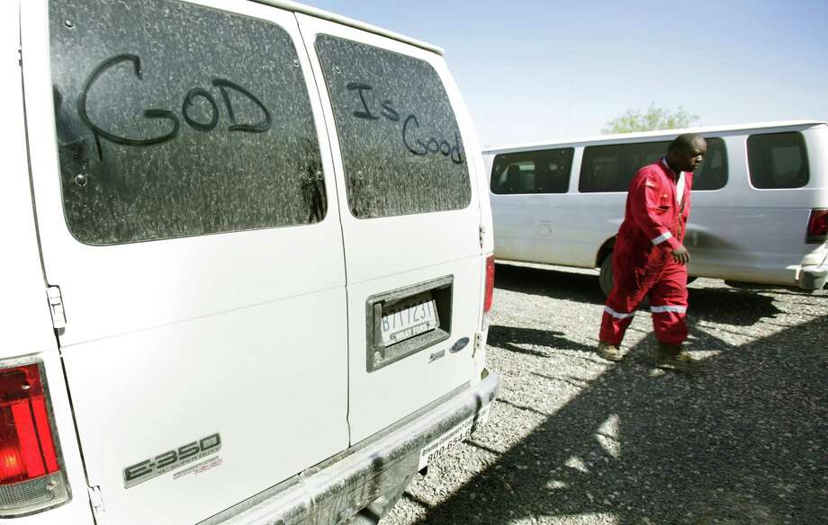 A Halliburton worker walks to the dining hall at Wotel One worker lodge, passing a company van on which someone left a message.  Churches are facing challenges in ministering to the Eagle Ford workers. Photo: Bob Owen, Staff / © 2012 San Antonio Express-News