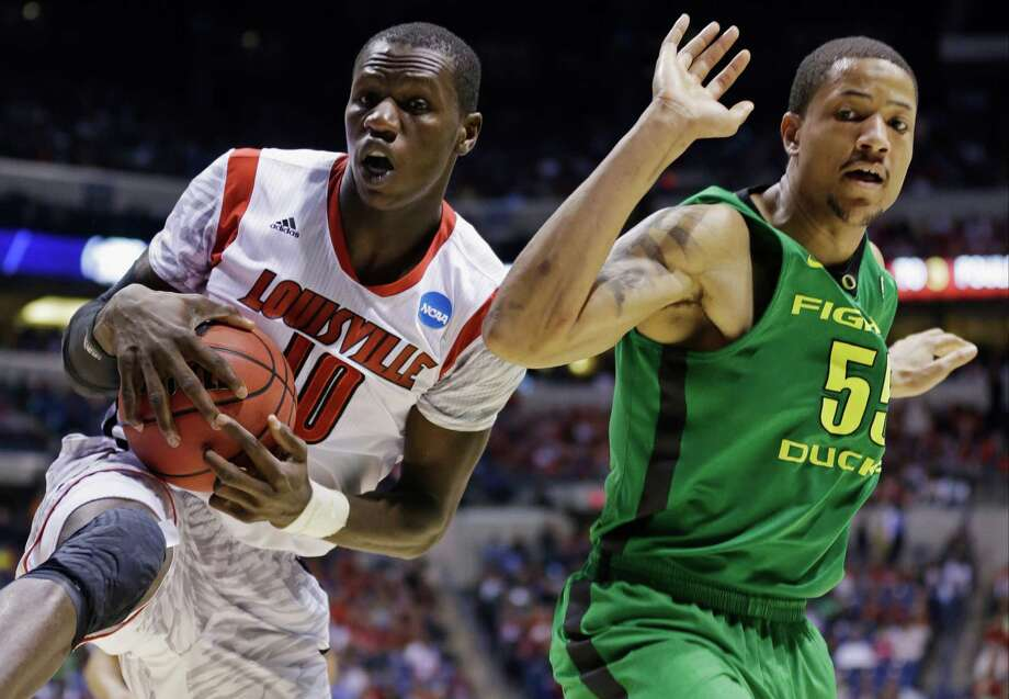 Louisville center Gorgui Dieng (10) grabs a rebound against Oregon center Tony Woods (55) during the second half of a regional semifinal in the NCAA college basketball tournament, Friday, March 29, 2013, in Indianapolis. (AP Photo/Michael Conroy) Photo: Michael Conroy, Associated Press / AP