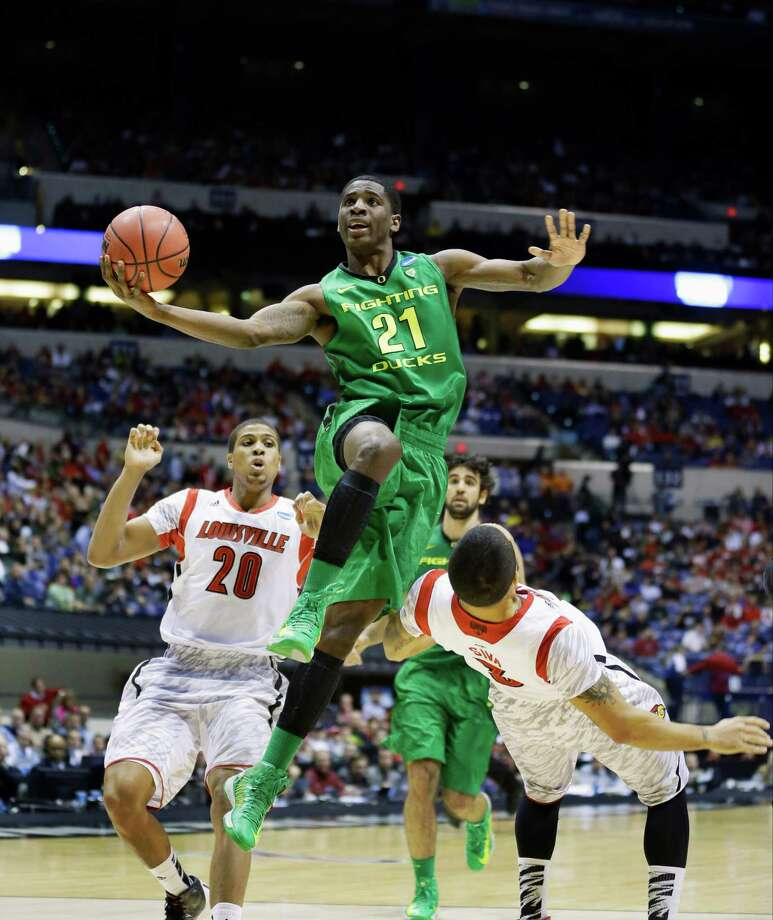 Oregon guard Damyean Dotson (21) goes up with a shot under pressure from Louisville guard Peyton Siva (3) during the second half of a regional semifinal in the NCAA college basketball tournament, Friday, March 29, 2013, in Indianapolis. Dotson was called for an offensive foul on the play.  (AP Photo/Michael Conroy) Photo: Michael Conroy, Associated Press / AP