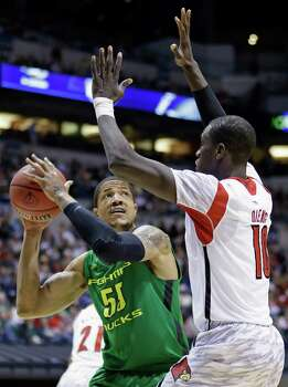 Oregon center Tony Woods (55) looks to shoot against Louisville center Gorgui Dieng (10) during the second half of a regional semifinal in the NCAA college basketball tournament, Friday, March 29, 2013, in Indianapolis. (AP Photo/Michael Conroy) Photo: Michael Conroy, Associated Press / AP