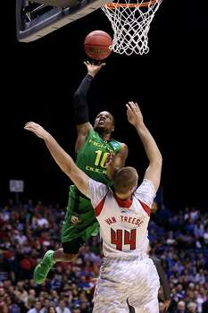 INDIANAPOLIS, IN - MARCH 29:  Johnathan Loyd #10 of the Oregon Ducks drives for a shot attempt in the first half against Stephan Van Treese #44 of the Louisville Cardinals during the Midwest Region Semifinal round of the 2013 NCAA Men's Basketball Tournament at Lucas Oil Stadium on March 29, 2013 in Indianapolis, Indiana. Photo: Streeter Lecka, Getty Images / 2013 Getty Images